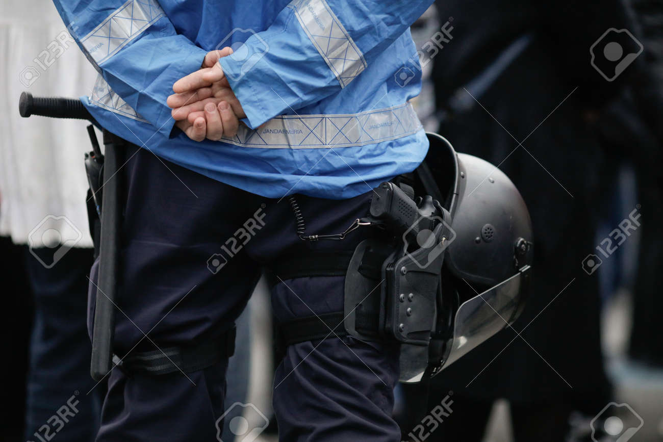 Bucharest, Romania - April 3, 2021: Details with the riot kit of a Romanian jandarm during a rally: gun, helmet, radio station, baton. - 167252061