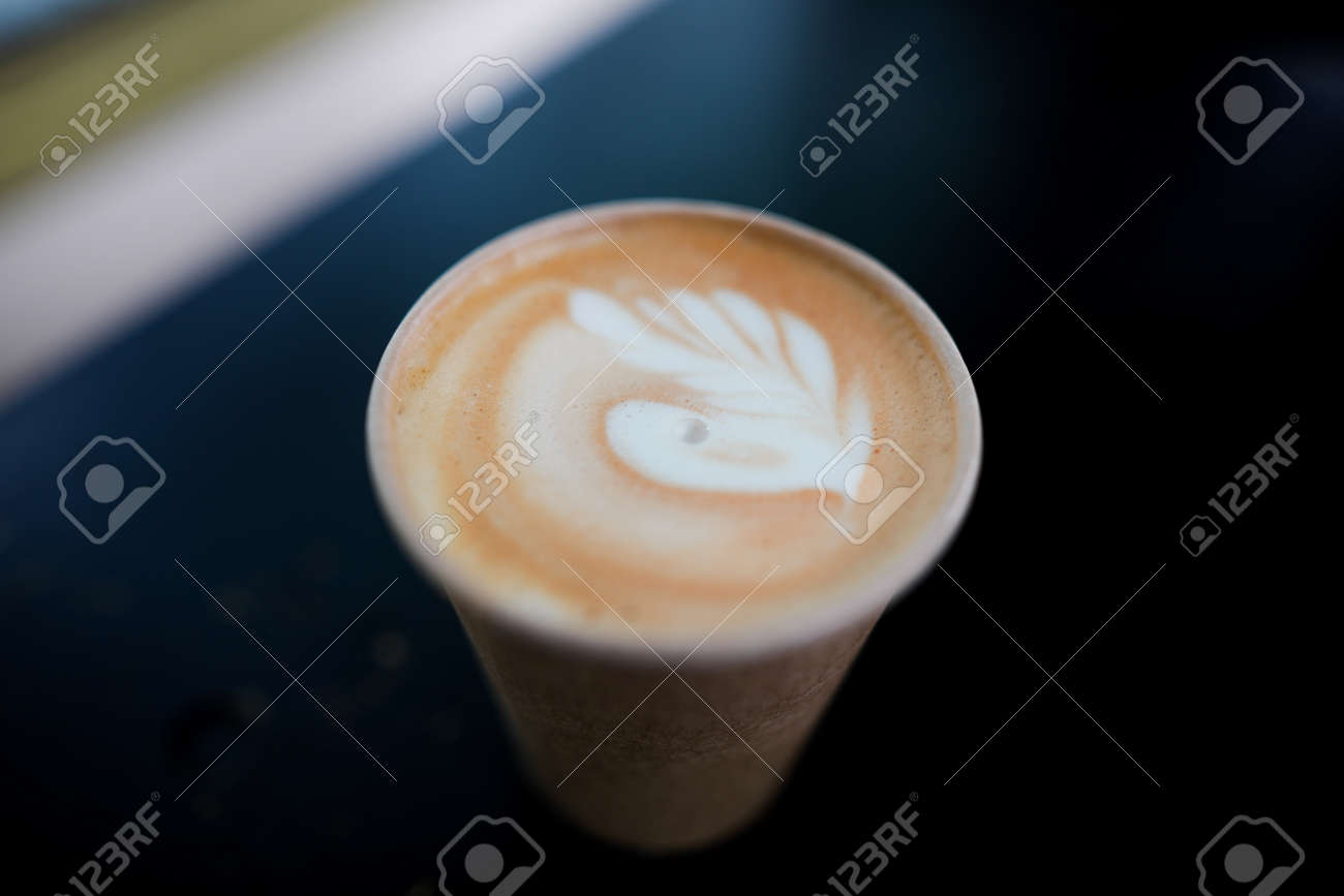 Shallow depth of field (selective focus) image with details of a decorated coffee in a paper cup. - 167007788