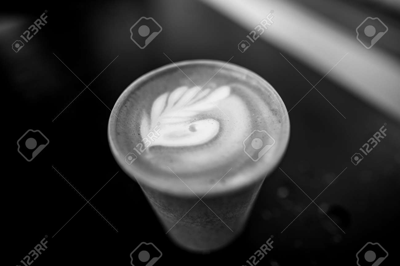 Shallow depth of field (selective focus) image with details of a decorated coffee in a paper cup. - 167266237