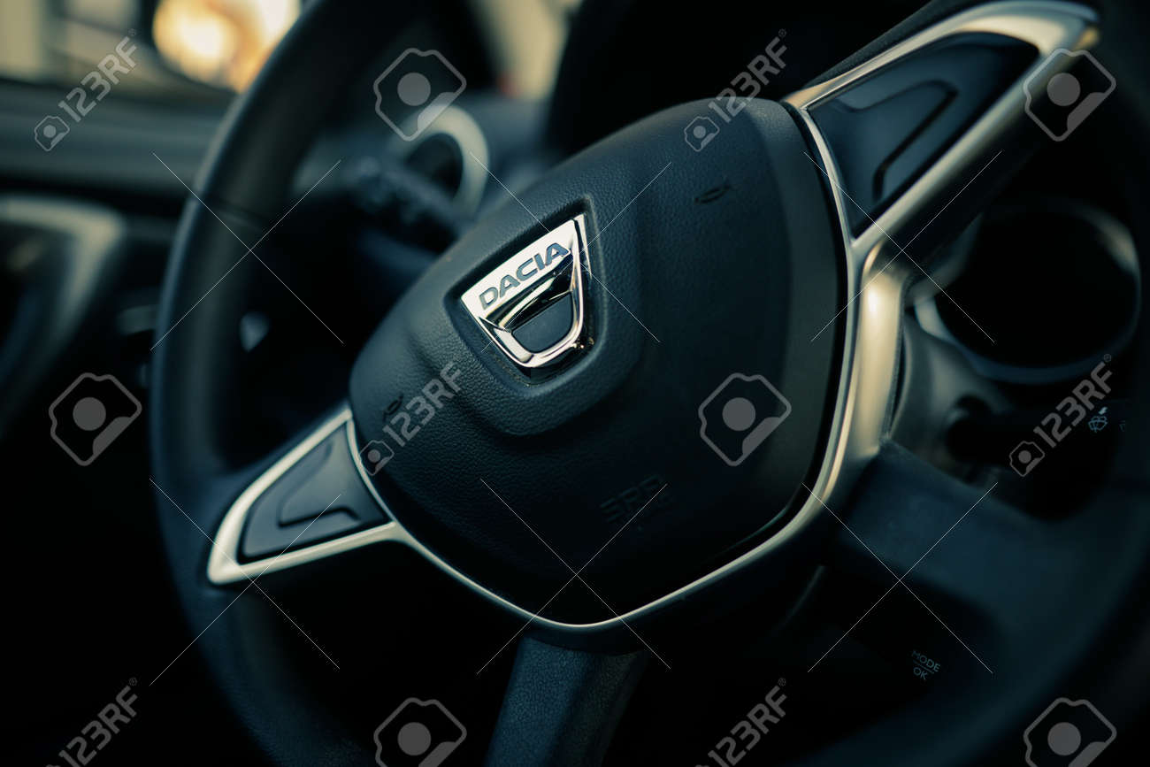 Bucharest, Romania - April 11, 2021: Shallow depth of field (selective focus) image with the Dacia logo on a Duster steering wheel. - 167598379
