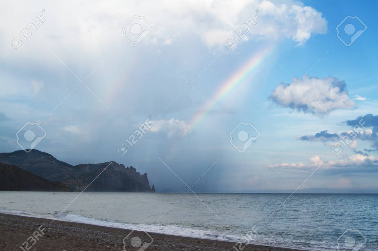 Rain over the sea with a beautiful rainbow Stock Photo - 9738034