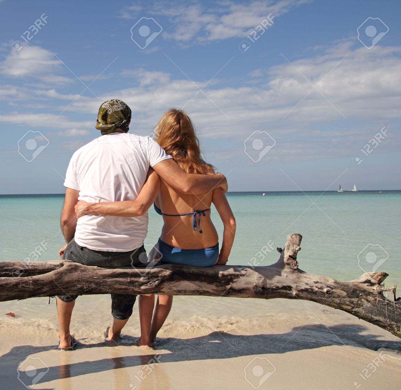 couple sitting on a tree watching at the ocean Stock Photo - 11874511