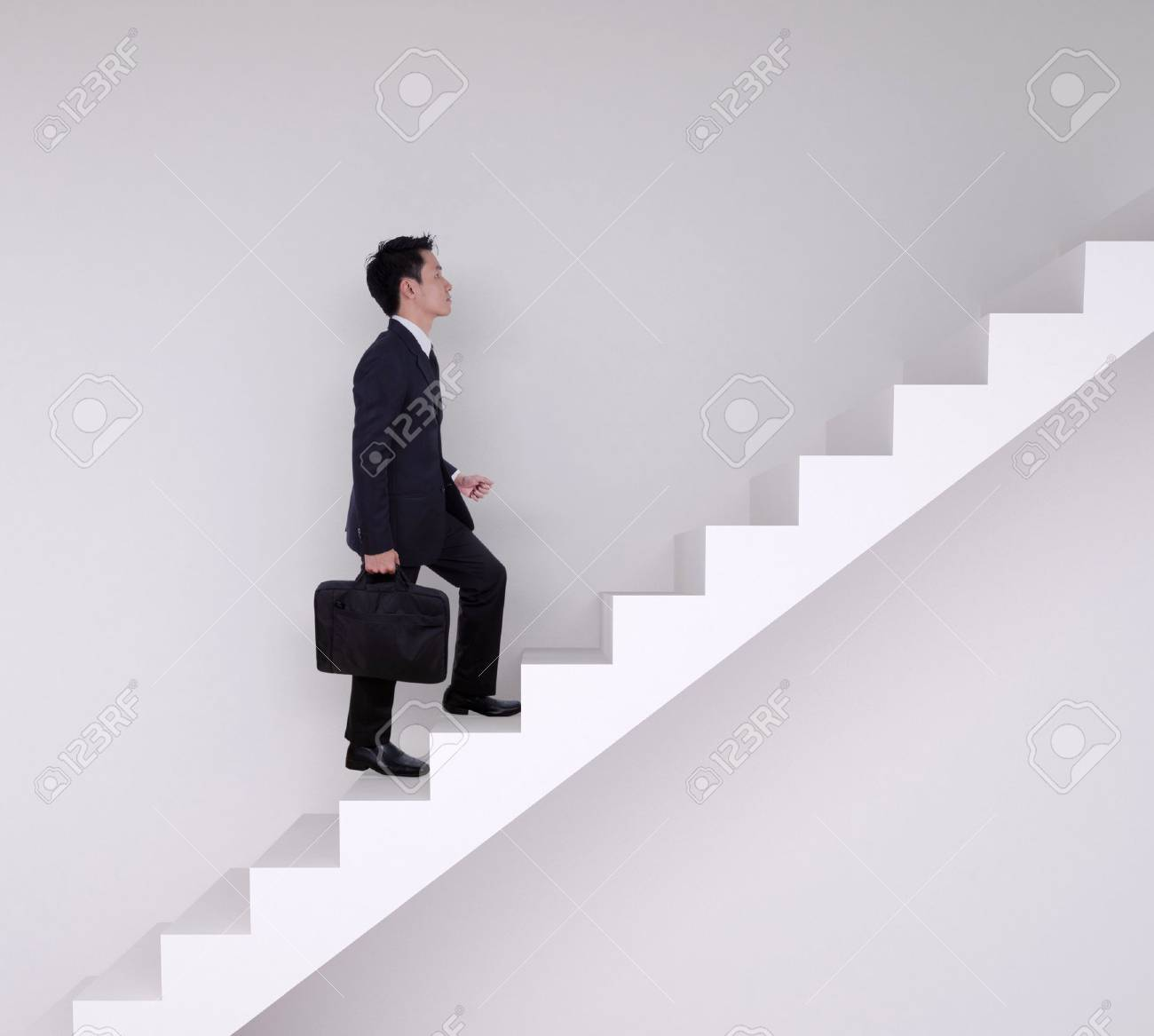 Business man stepping up on stairs with wall background - 52204264