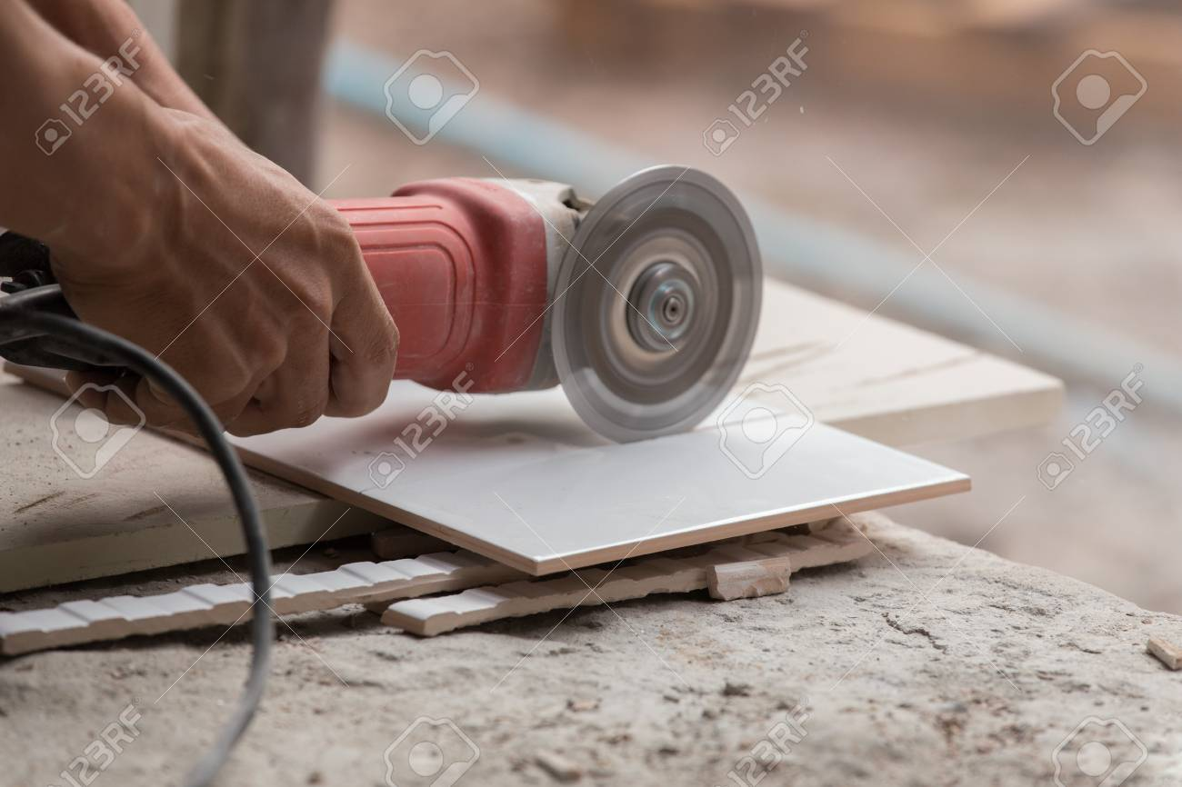 Worker cutting a tile using an angle grinder at construction stock stock photo worker cutting a tile using an angle grinder at construction site dailygadgetfo Choice Image