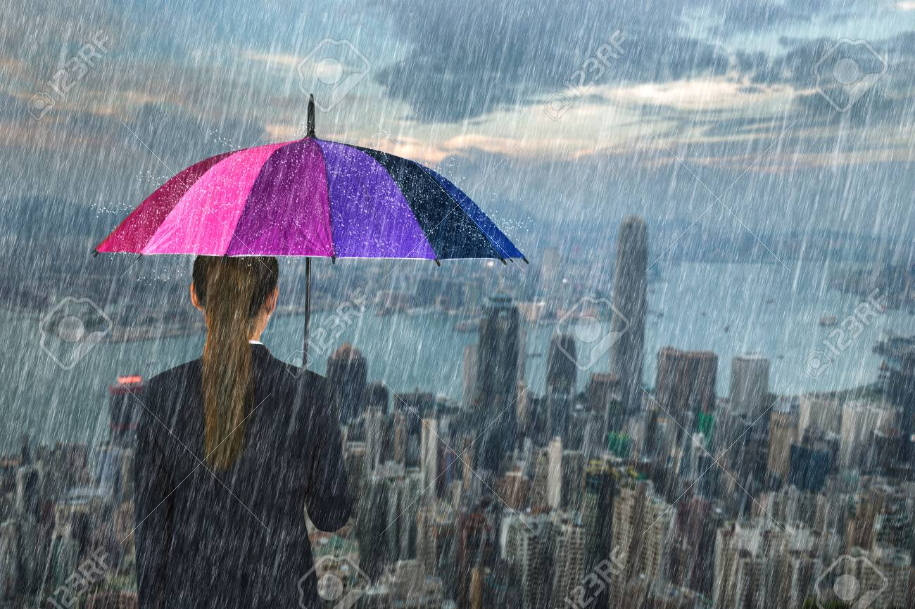 business woman holding multicolored umbrella with falling rain