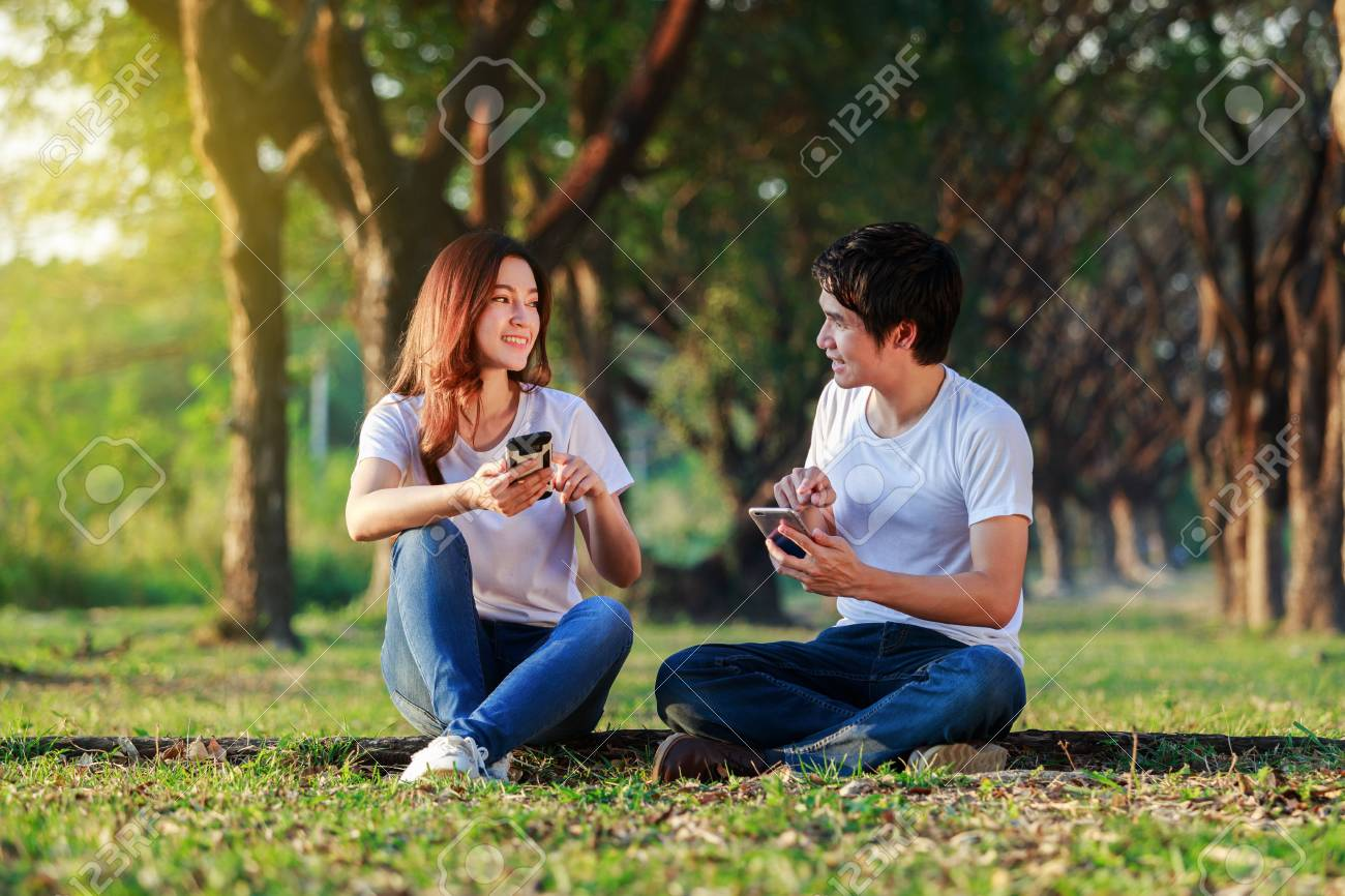 couple using mobile phone and talking in the park - 95604572