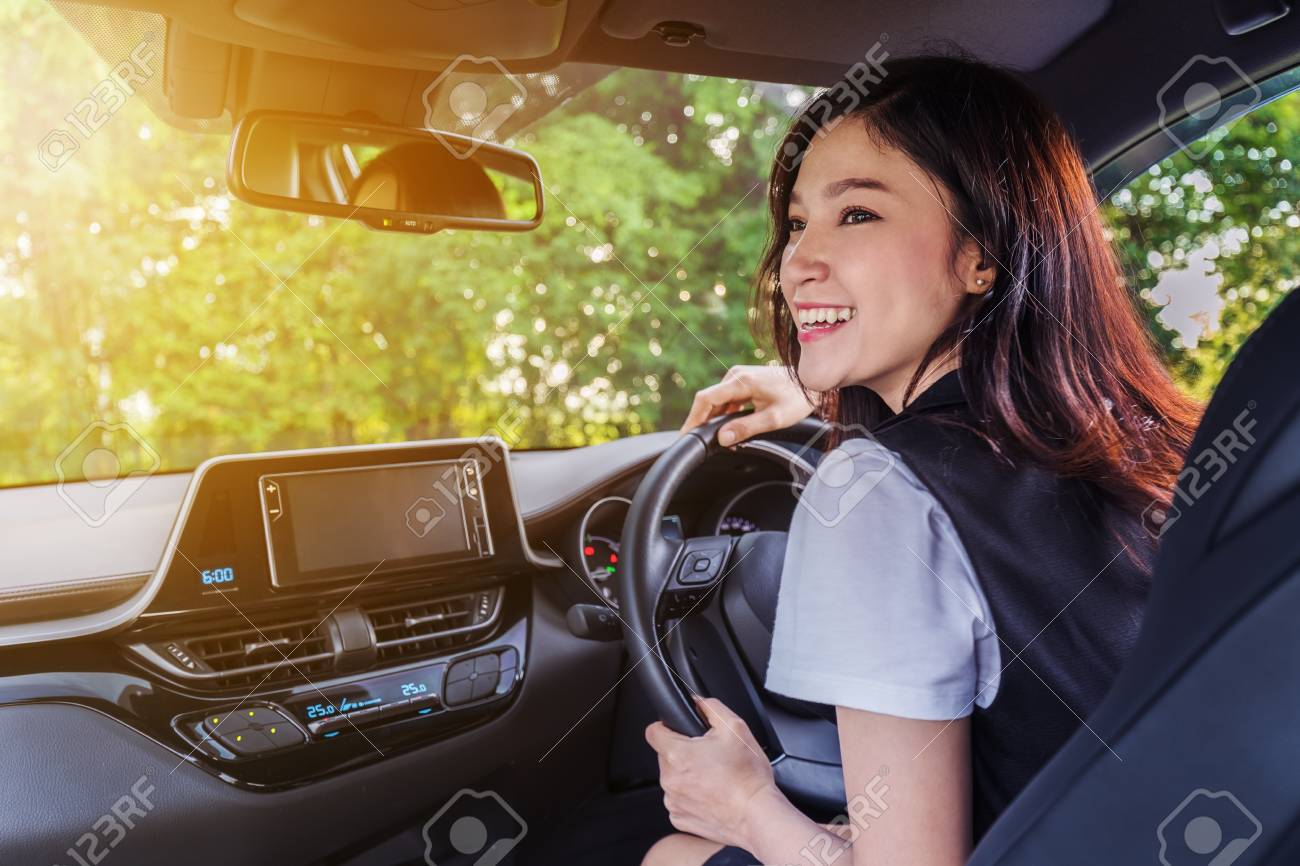 happy young woman in a car - 107583164