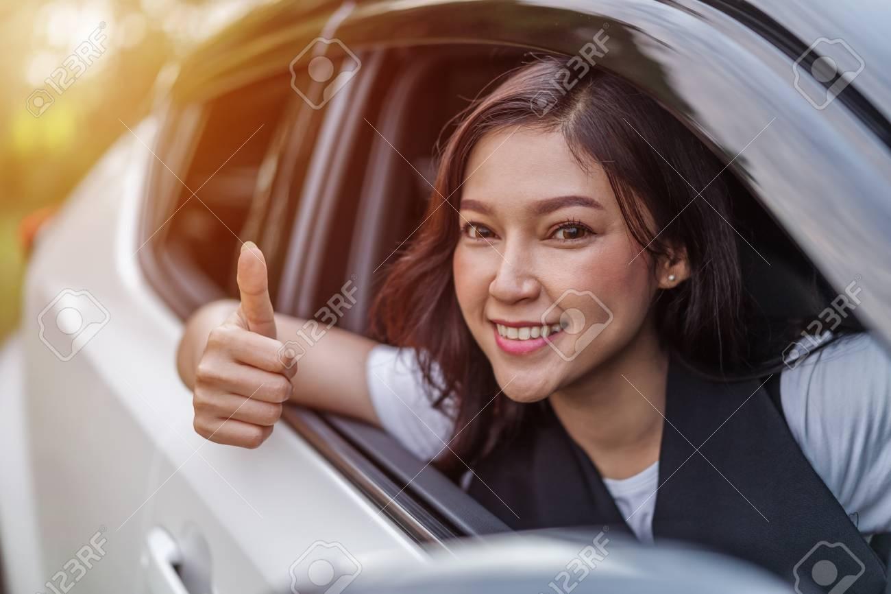 beautiful woman giving thumb up inside her car - 107619790