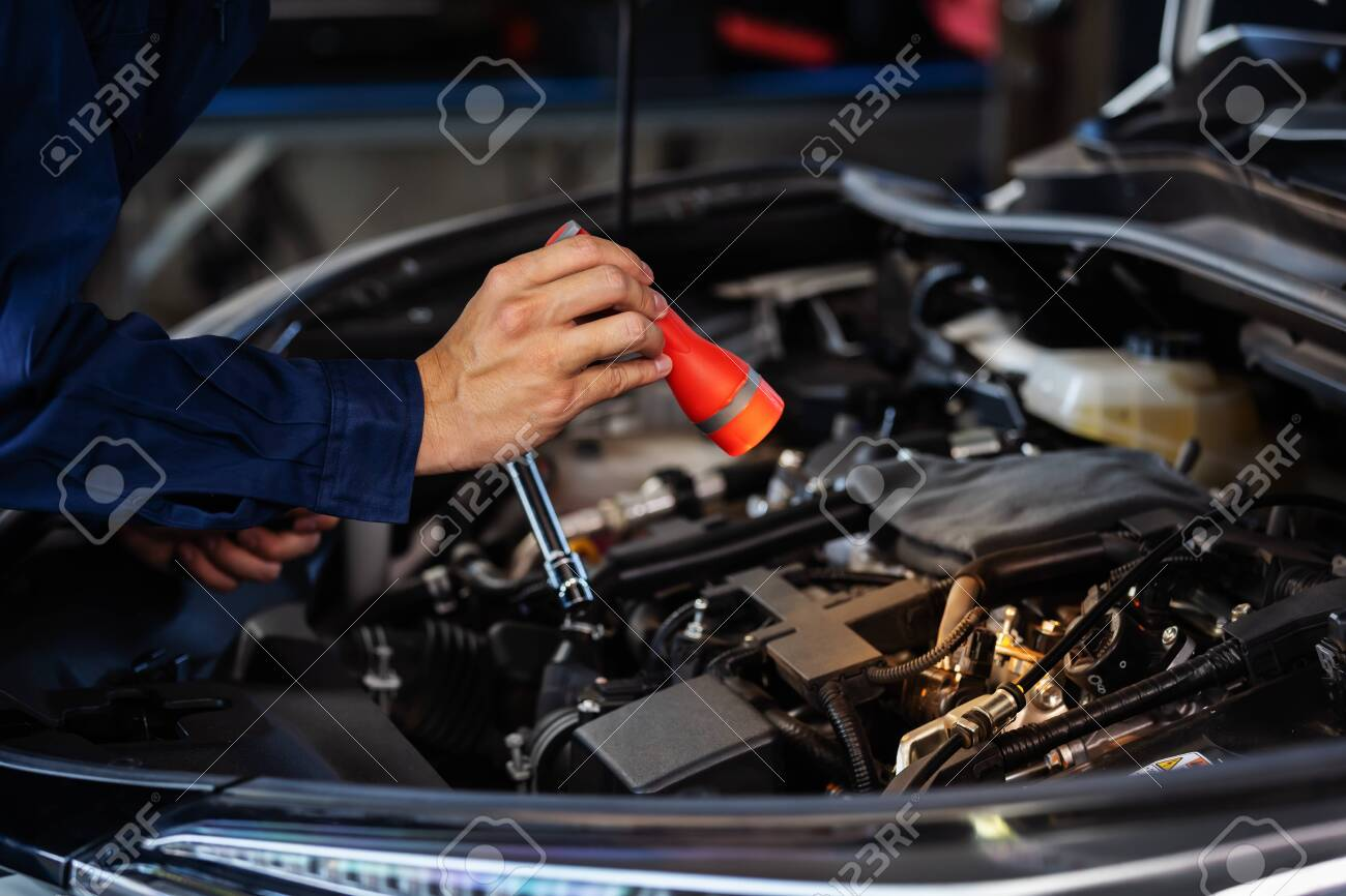 male mechanic holding and shining flashlight to checking a car engine problem - 142546026