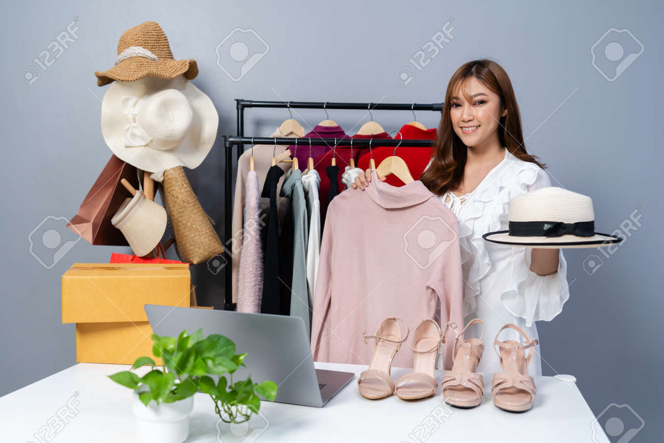 young woman selling clothes and accessories online live streaming, business online e-commerce at home - 166337525