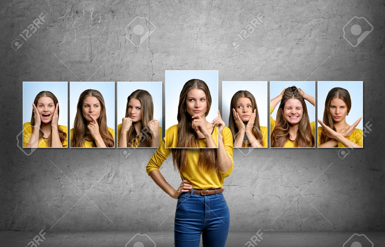 Young beautiful girl holds and changes her face portraits with different emotions. - 55737031