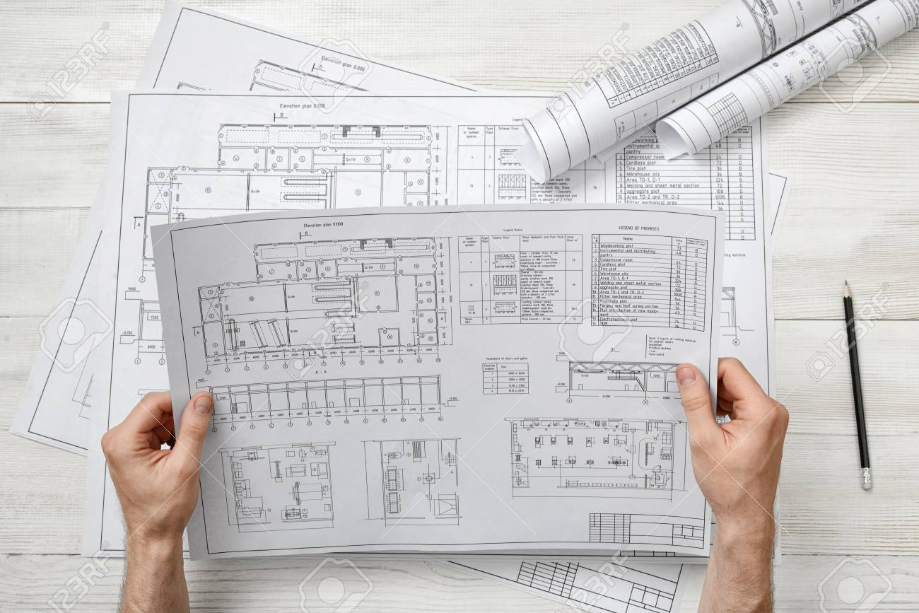 Hands Of Architect Holding A Drawing Sketch Workplace Of Architect Stock Photo Picture And Royalty Free Image Image 56344568