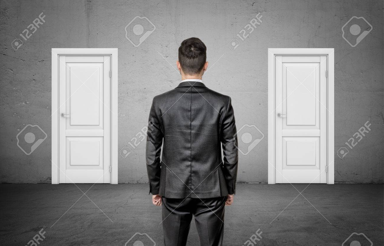 A businessman with his back turned stands between two identical closed white doors. - 85241147