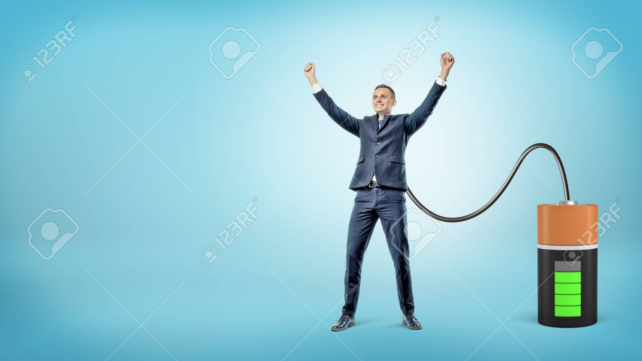 A happy businessman with raised hands is connected to a large battery charging him. - 89945445