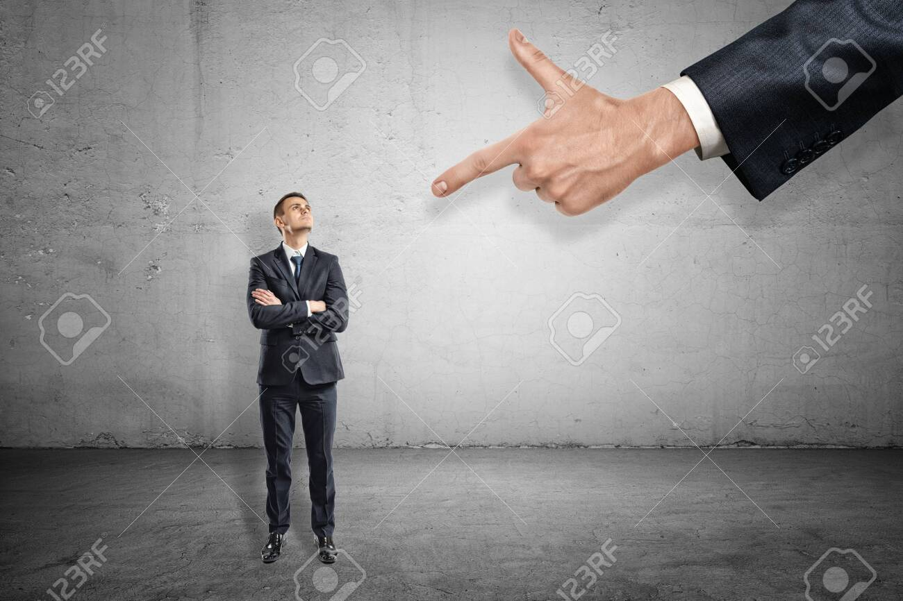 Front full length view of little businessman standing and looking up at huge hand pointing index finger at him. - 123507864