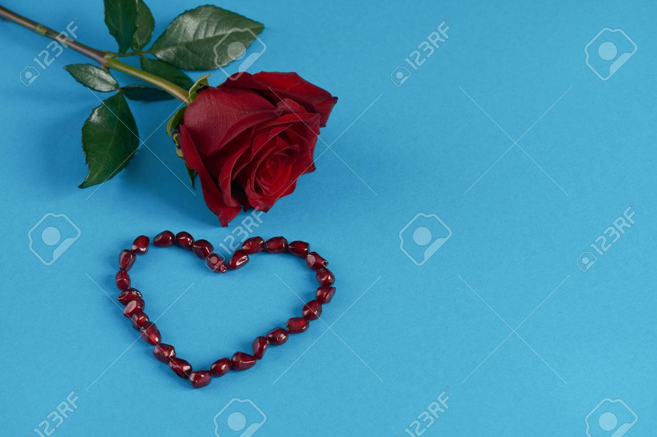 Pomegranate seeds shaped as heart and rose flower on blue paper pomegranate seeds shaped as heart and rose flower on blue paper background love card concept mightylinksfo