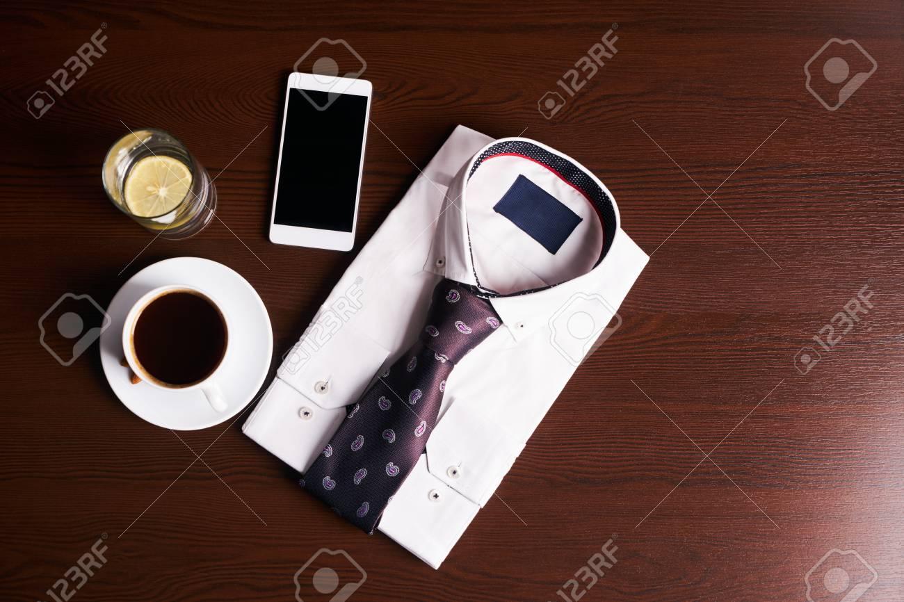07922df99b2106 Archivio Fotografico - Set di moda uomo e accessori, camicia leggera con  cravatta, telefono cellulare, tazza di caffè caldo e bicchiere d'acqua con  limone ...