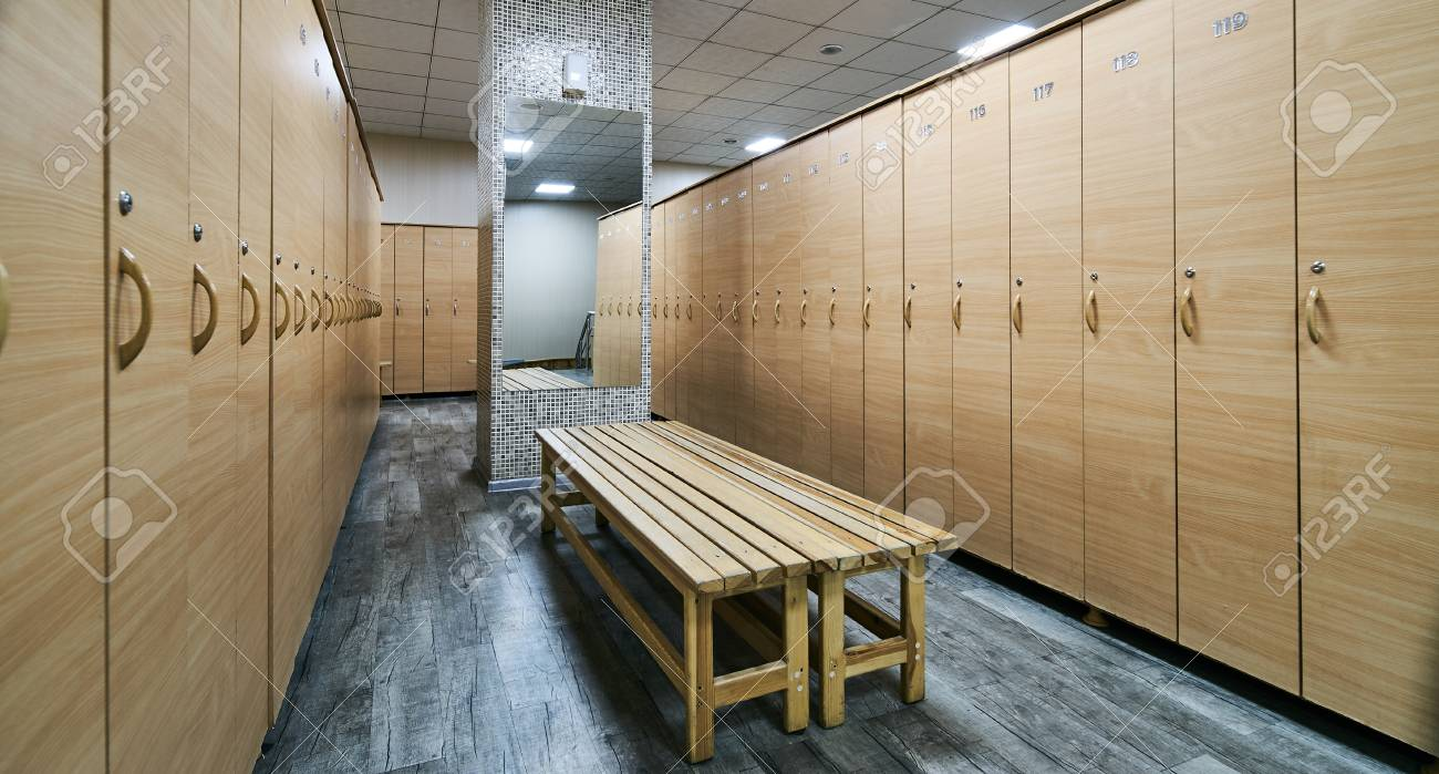 Wooden lockers with a wood bench in a locker room with doors