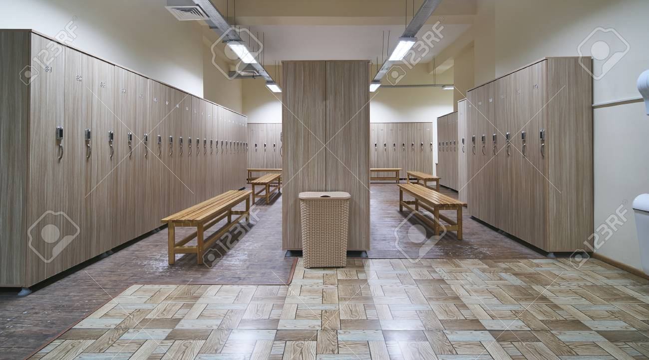 Locker room with wood benches and wooden lockers in the gym stock