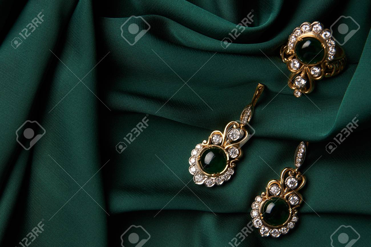 Beautiful Golden Ring And Pair Of Earrings With Green Emerald Diamonds Gemstones On A