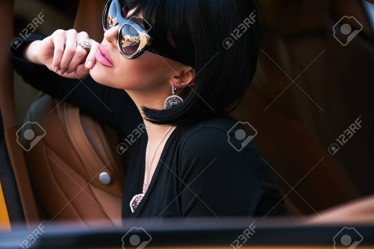 Portrait of Glamour brunette babe sitting in yellow supercar. Young woman  with black hair and 6e97c4ad4