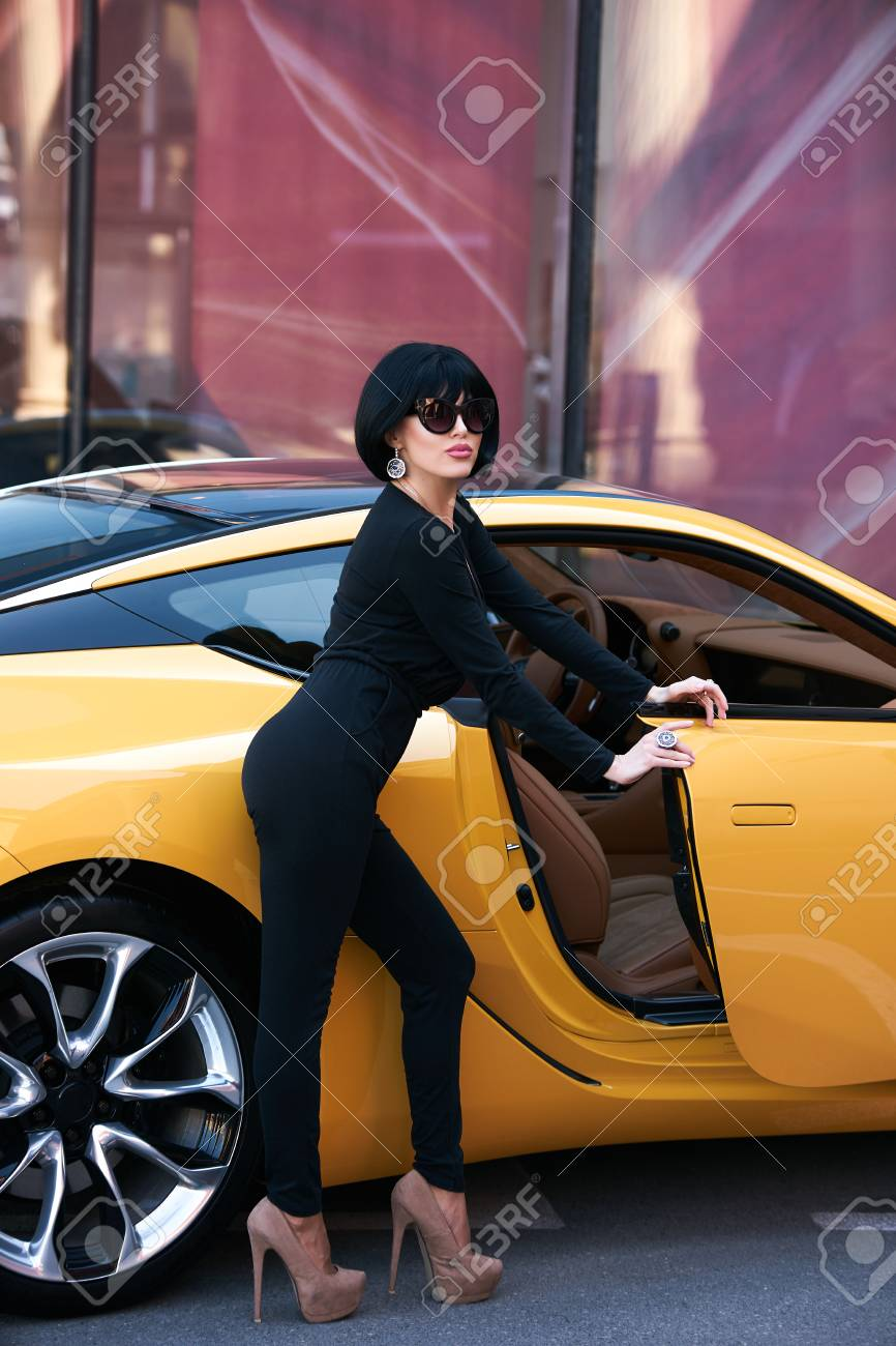 ... sunglasses posing near supercar. Beautiful brunette woman with yellow  sport car. Young woman with dark hair in black bodysuit d992f4e17