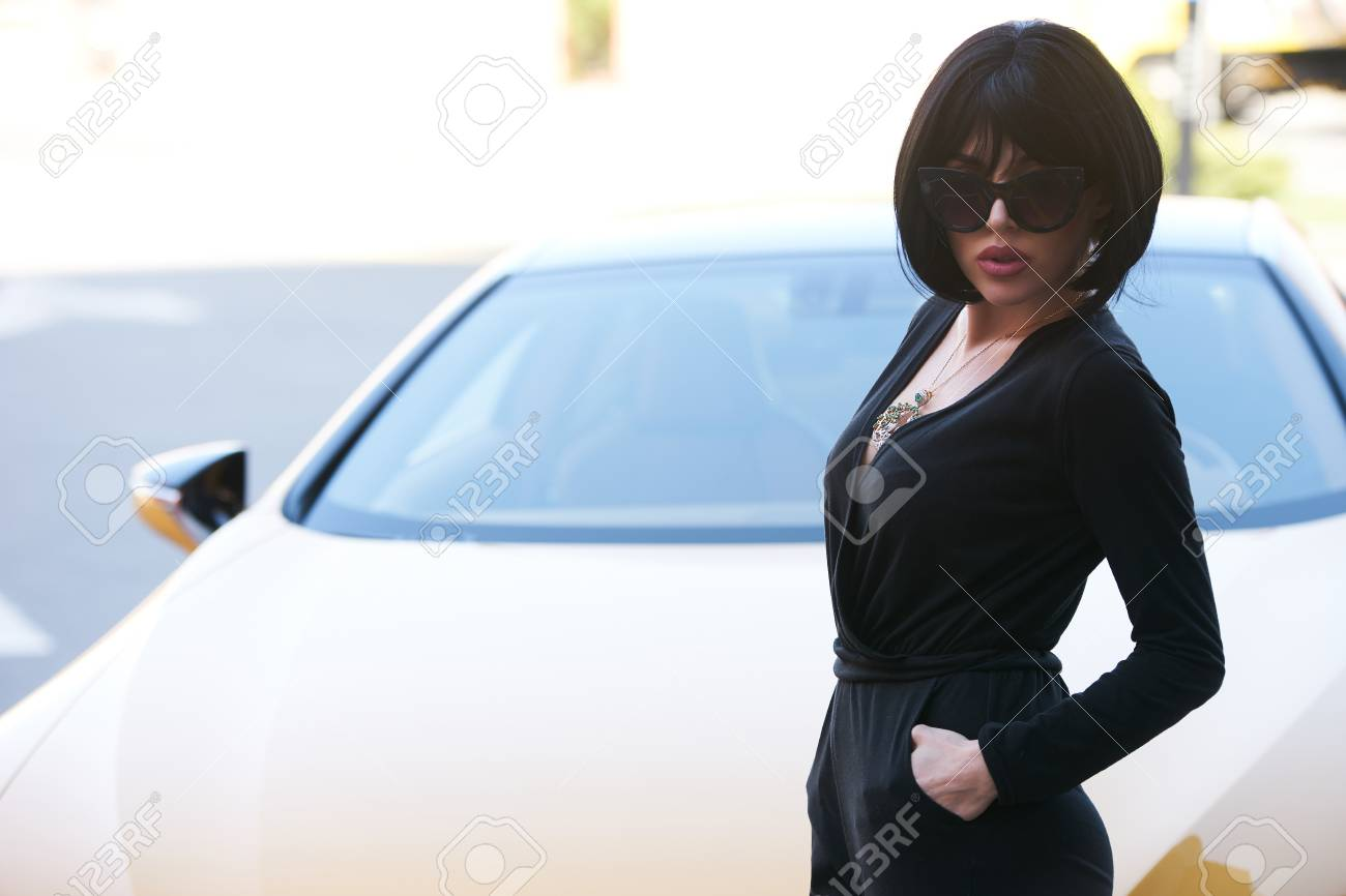 Beautiful young woman with dark hair in black bodysuit and sunglasses  posing near yellow supercar. 791fc10bf