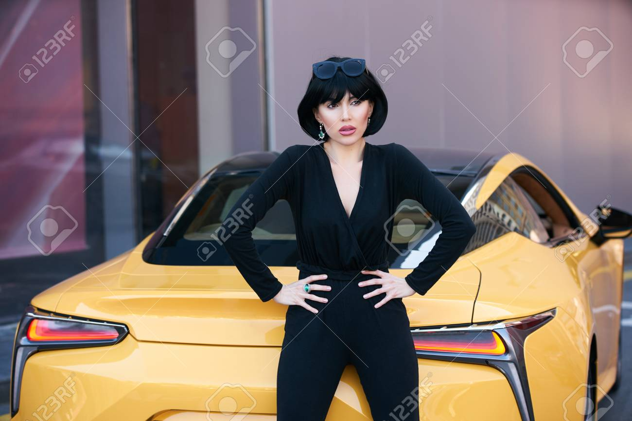 Stock Photo - Young woman with dark hair in black bodysuit and sunglasses  posing near supercar. Portrait of a Beautiful brunette woman with yellow  sport car 6915efc64