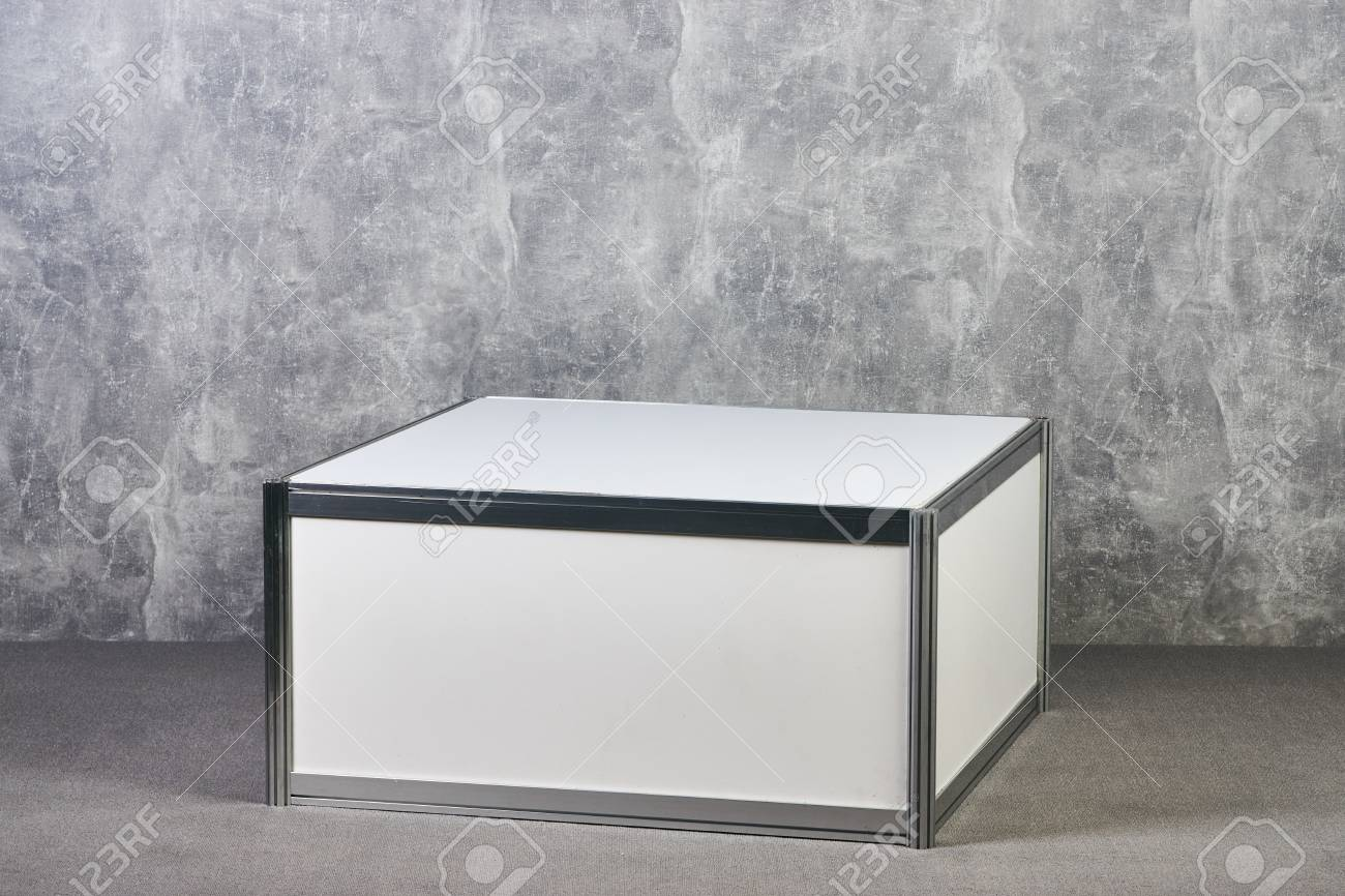 Stock photo white showcase stand against gray textured wall background international exhibition furniture elements in large warehouse interior