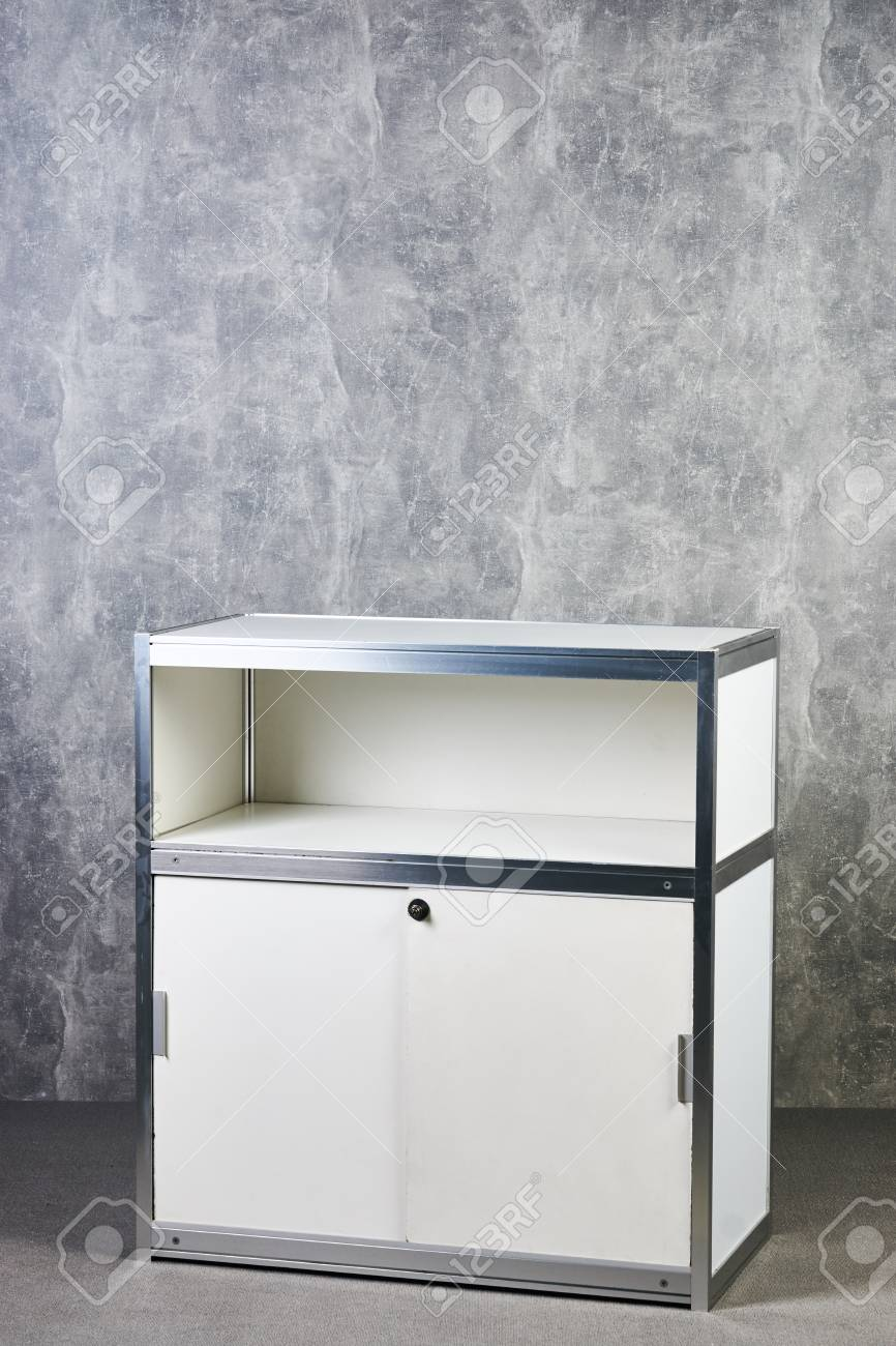 Stock photo white glass showcase stand against gray textured wall background international exhibition furniture elements in large warehouse interior