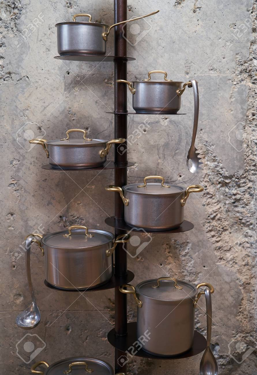 Kitchen pan holder stand on concrete wall with copy space. Stainless..