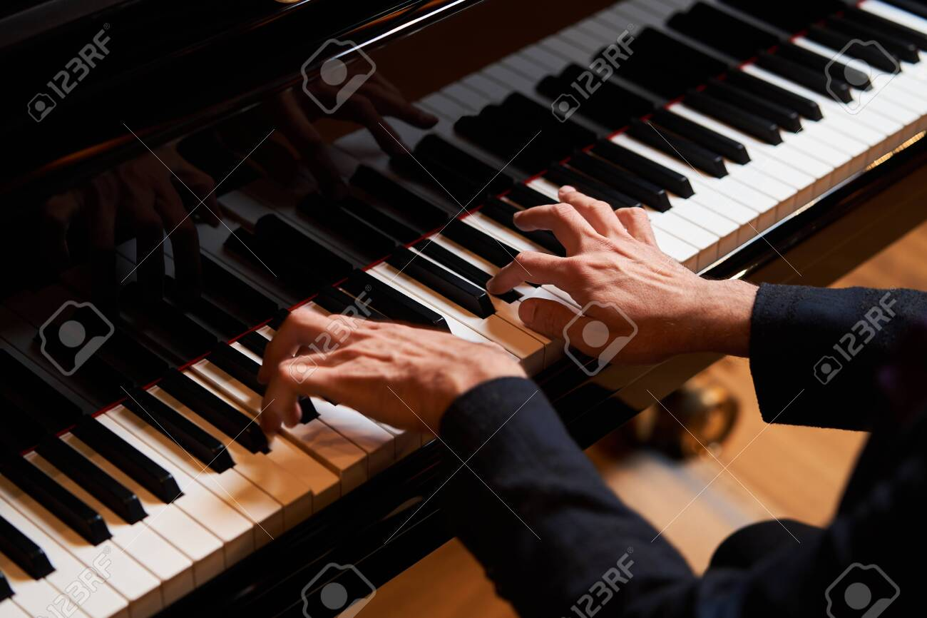 Closeup man's hand playing piano. Music performer's hand playing the grand piano keyboard - 130485375