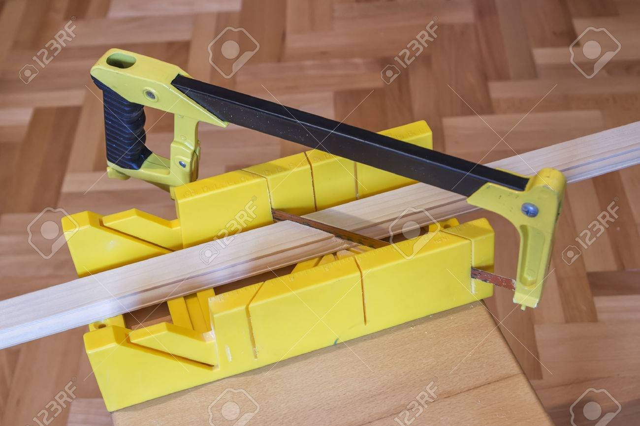 Using Hand Saw And Miter Box For 45 Degree Cutting Stock Photo