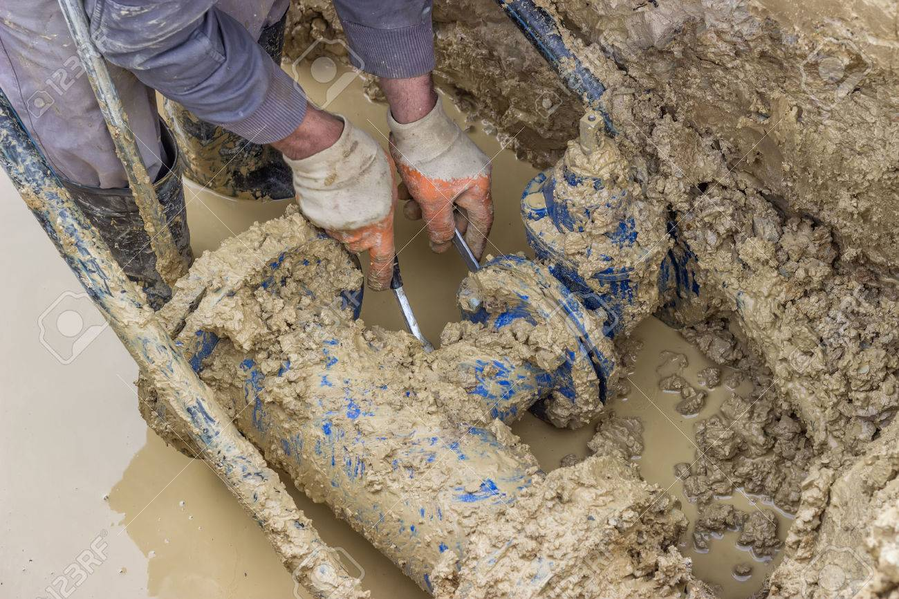 Stock Photo - Utility worker using tool to repair the broken pipe valve for commercial building water supplies. Utility worker fixing broken water main. & Utility Worker Using Tool To Repair The Broken Pipe Valve For ...