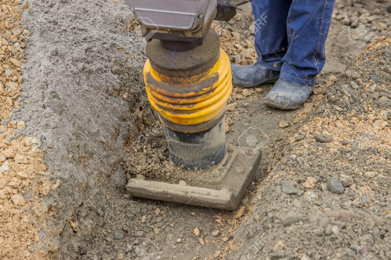 travailleur compacter le lit de sable avec pilon mécanique le long