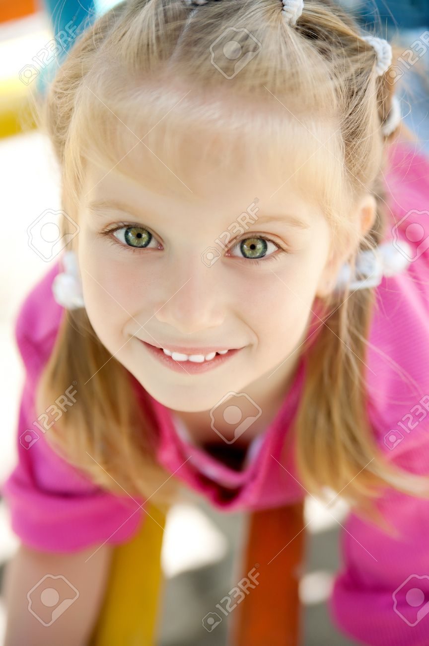 fa538edc7b2f Cute Little Girl Smiling In A Park Close-up Stock Photo