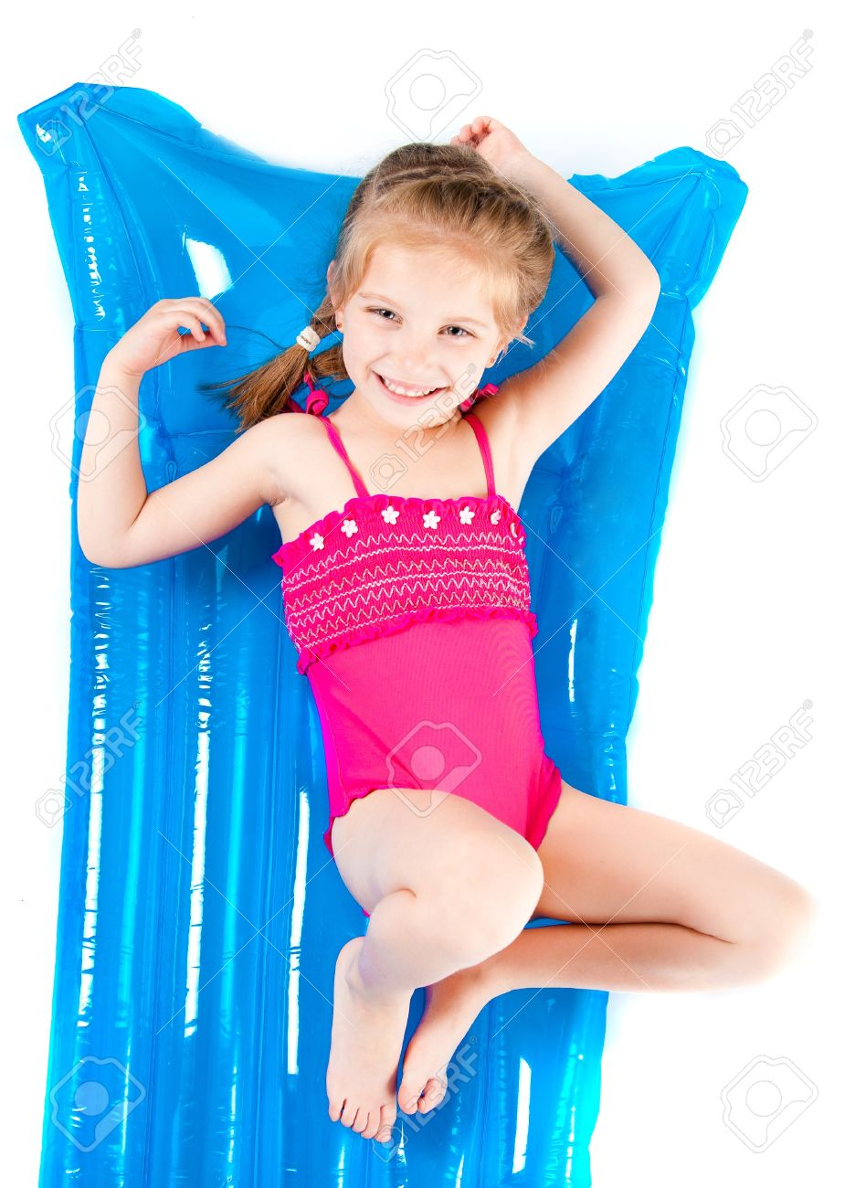 cute little girl in a swimming suit on an inflatable mattress stock