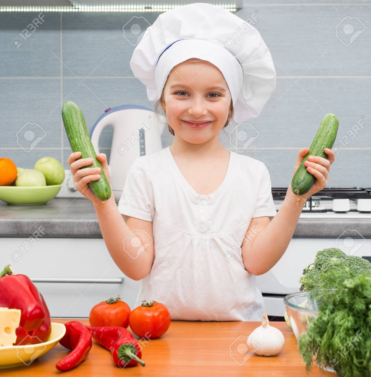 Little Girl In A Cap Chef In The Kitchen With Cucumbers Stock Photo ...