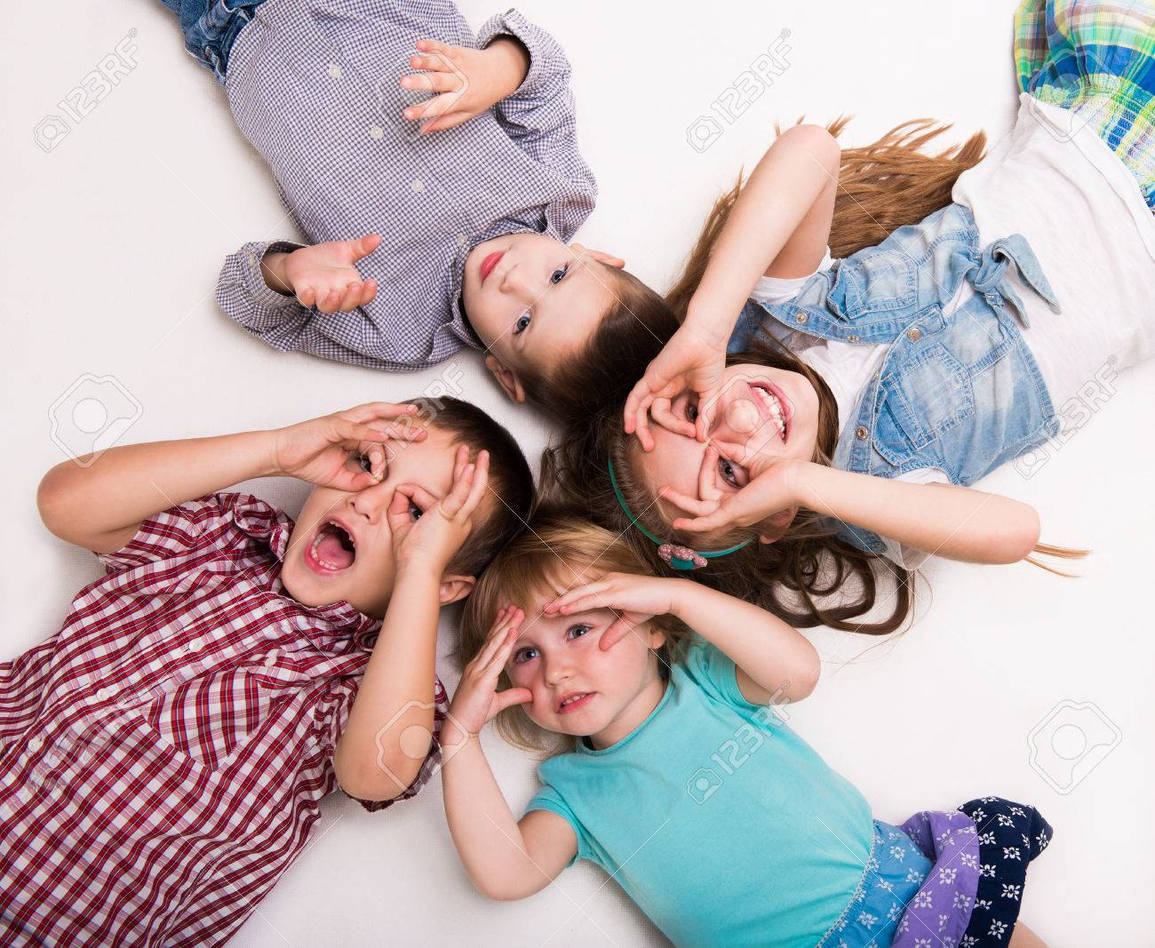 children lying on the floor with hands imitating glasses isolated on white background - 52204373