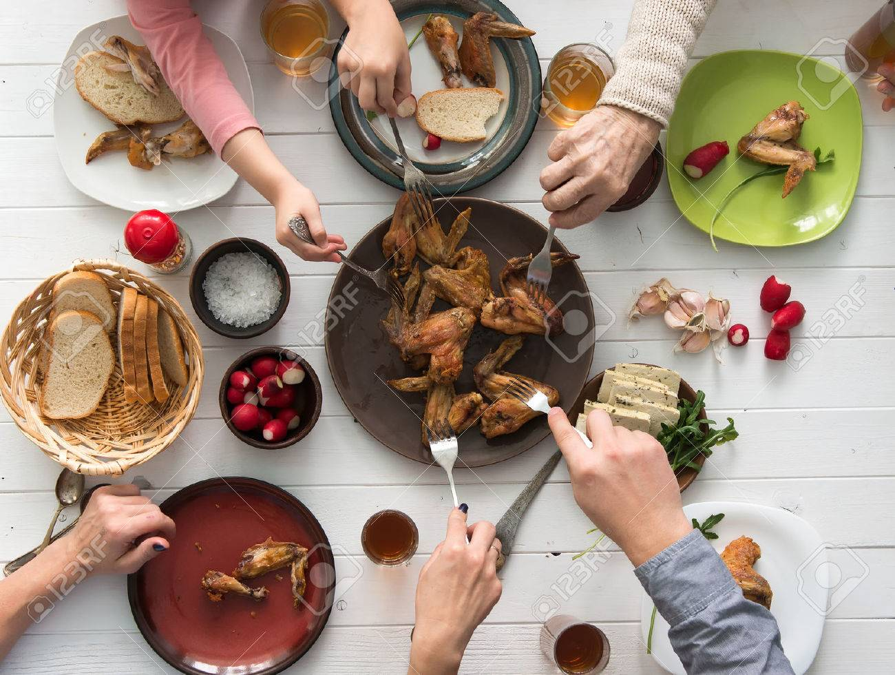 dinner table top view. dinner table top view: family having roasted chicken wings for view
