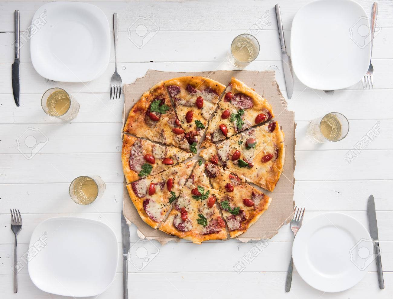 Stock Photo   Table With Pizza Set For Four Persons Top View