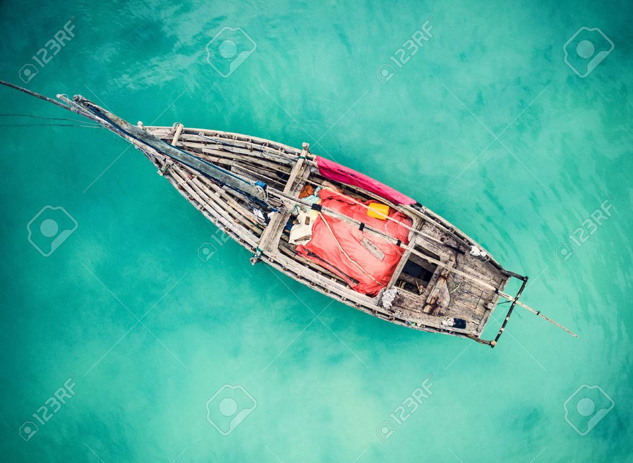 https://previews.123rf.com/images/gekaskr/gekaskr1705/gekaskr170500143/77658198-lonely-fishing-boat-in-clean-turquoise-ocean-aerial-photo-top-view.jpg