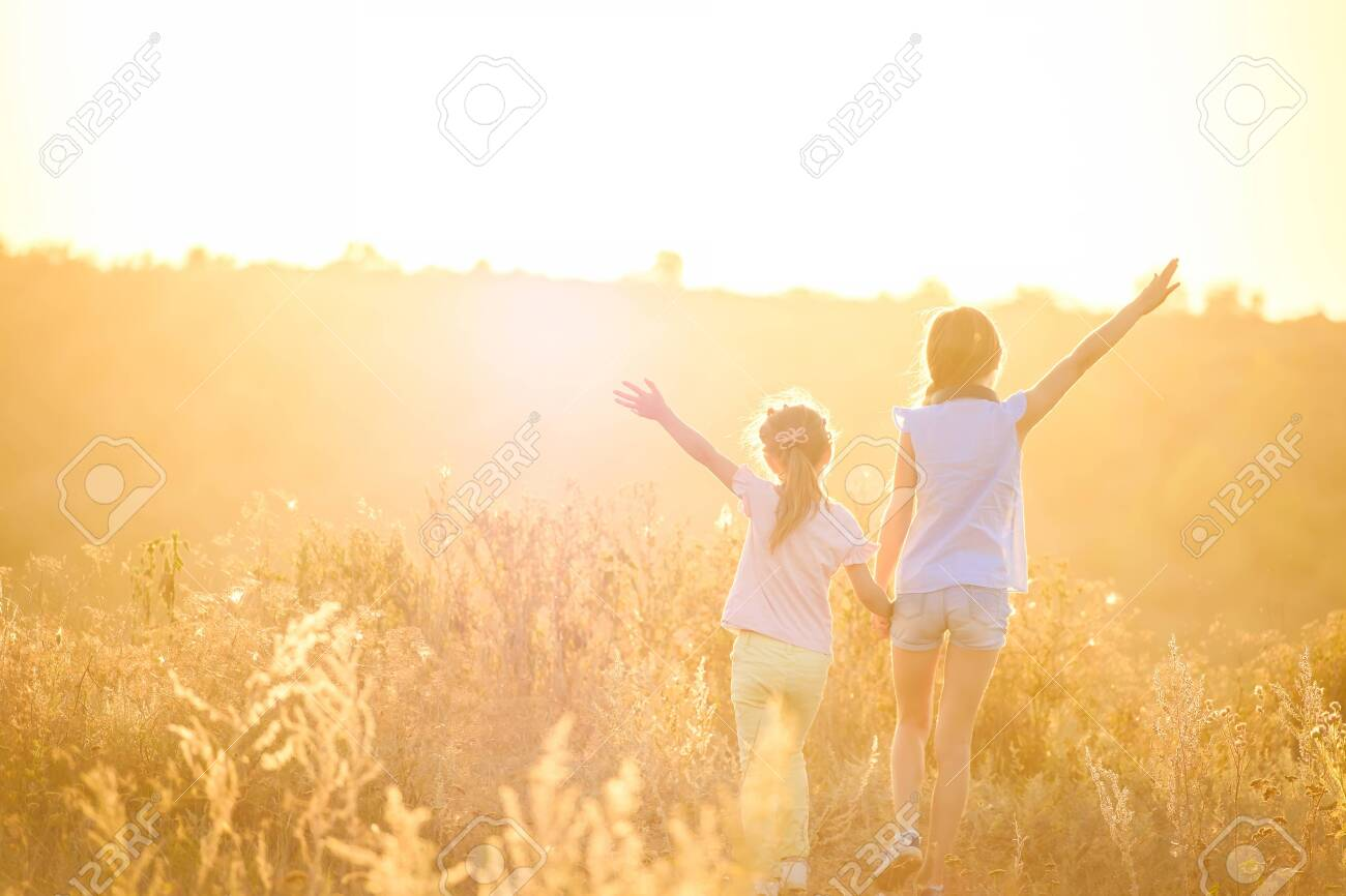 Little girls stand by holding hands looking on sunshine evening field with joyfully raised hands - 123885981