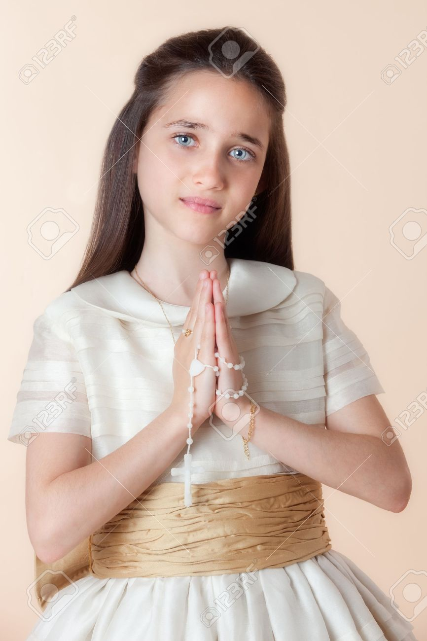 Pretty girl on the day of their communion in prayer with the rosary in his hands Stock Photo - 6981717