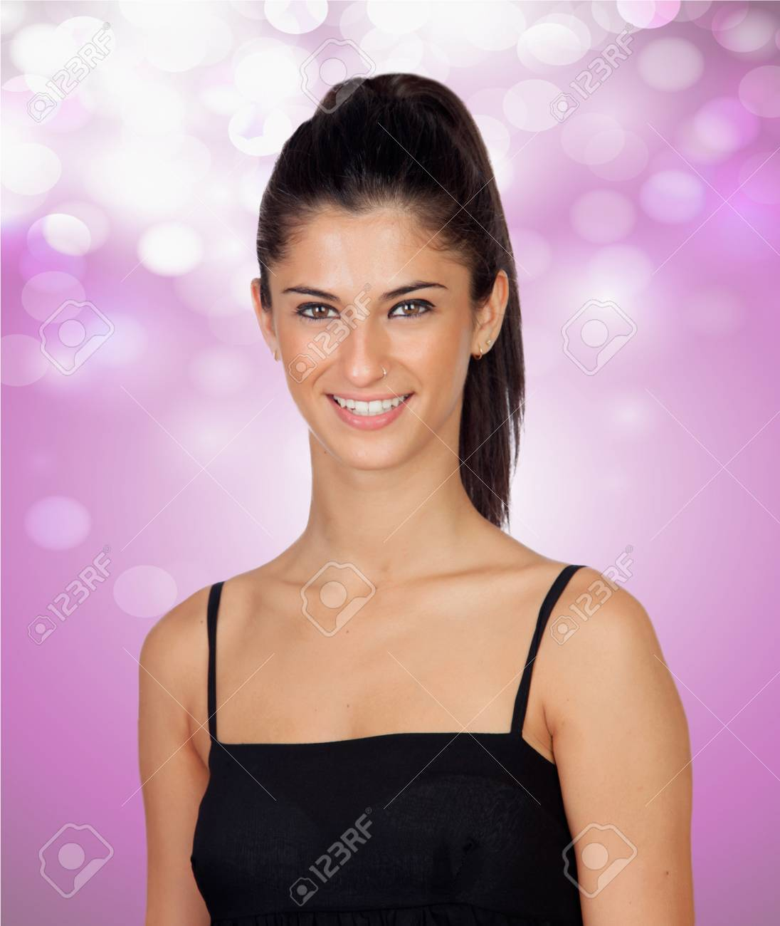 Attractive brunette girl with a pierced nose on a pink and bright background Stock Photo - 20310285