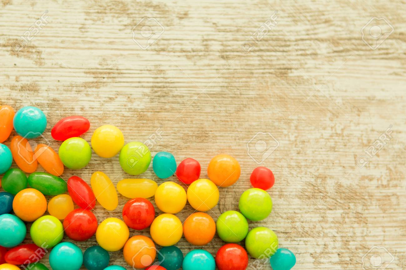Colorful Jelly Beans Of Different Sizes Close To Wallpaper Stock Photo