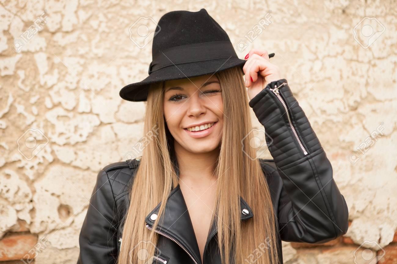 7f28c2aaa31 Y Rubia Chaqueta Cuero Sombrero Ojo Un Joven Negro De Con Guiñando Aqq7FI