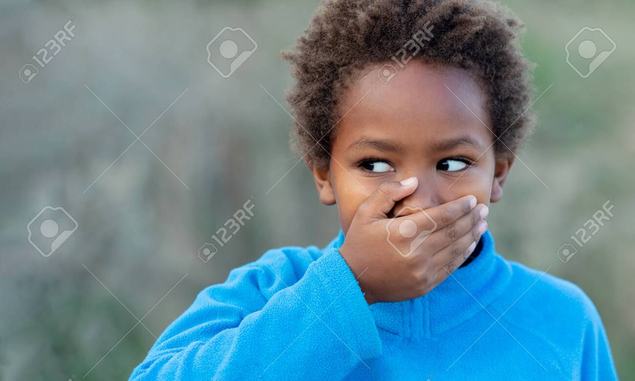 Little african boy covering his mouth with a blue jersey - 146978574