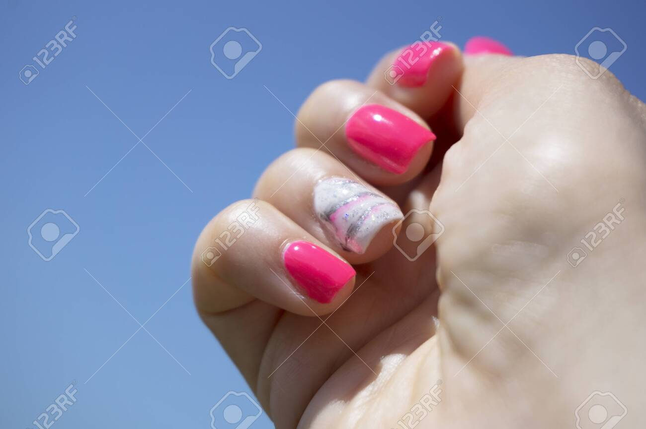 Womans hand showing her semipermanent manicure. Pink colour - 148033618