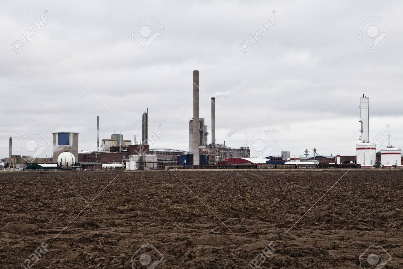 Industrial buildings behind a field on a cloudy day Stock Photo - 6090912